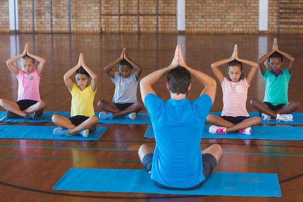 Bambini della scuola e insegnante che meditano durante la lezione di yoga