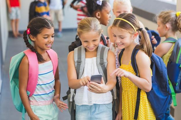 Bambini della scuola che utilizzano telefono cellulare nel corridoio