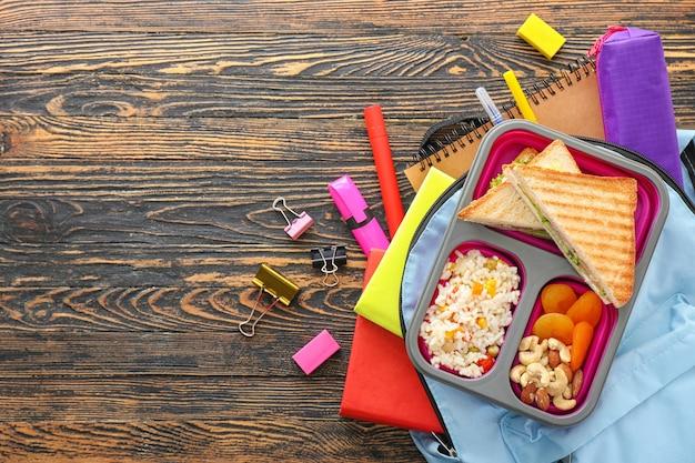 Scatola pranzo scuola, zaino e articoli di cancelleria su fondo in legno