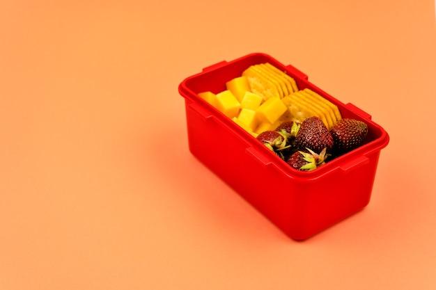 Pranzo a scuola con biscotti, pezzi di formaggio e fragole su uno sfondo arancione copia spazio