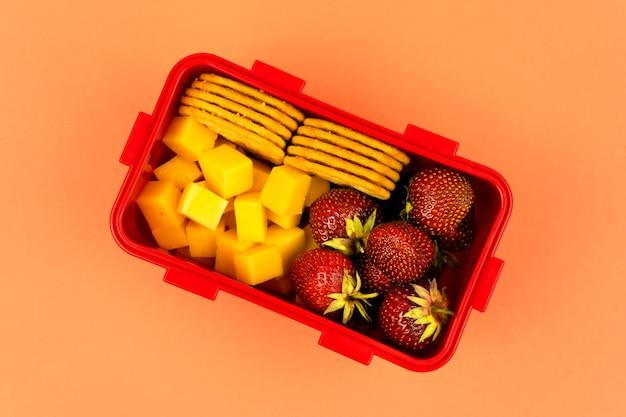 Pranzo a scuola con biscotti, pezzi di formaggio e fragole su uno sfondo arancione vista dall'alto