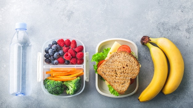 Scatola della refezione con la banana delle bacche delle verdure del panino sulla tavola grigia sana Foto Premium