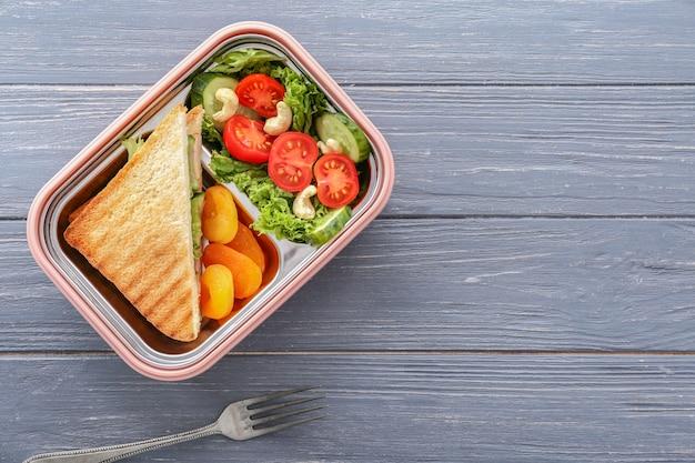 Scatola pranzo scuola con cibo gustoso su legno