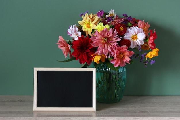 Mockup scolastico con lavagna giorno della conoscenza copia spazio composizione con un bouquet e una cornice vuota con uno sfondo nero sulla scrivania torna a scuola 1 settembre giorno dell'insegnante