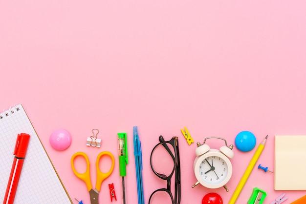 Quaderno scolastico e forniture per ufficio su sfondo rosa torna a scuola sfondo astratto bianco al...