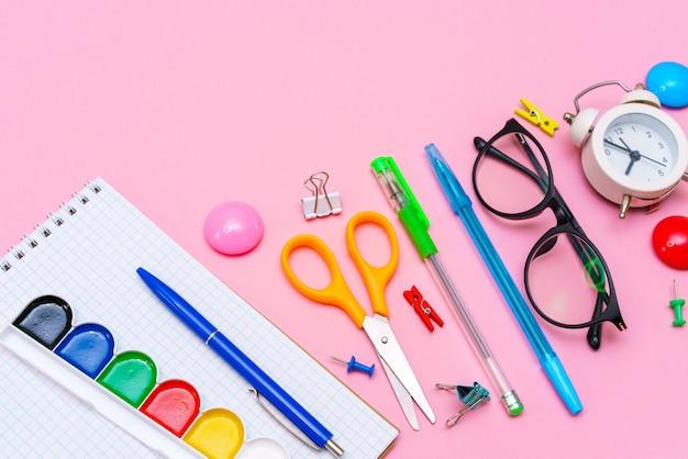Quaderno scolastico e varie forniture per ufficio torna al concetto di scuola forniture scolastiche luminose su un rosa ...