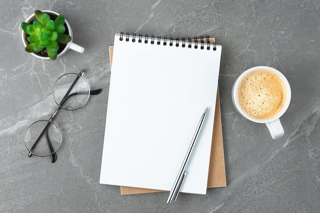 Quaderno di scuola con bicchieri e caffè sul tavolo sul tavolo di marmo. piatto concetto di business laici.