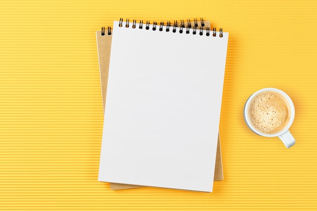 Quaderno di scuola con occhiali e caffè sul tavolo sul tavolo giallo. piatto concetto di business laici.