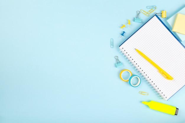 Articoli per ufficio della scuola su fondo blu. torna al concetto di scuola. vista dall'alto. copia spazio