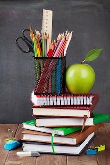 Forniture scolastiche e per ufficio sul tavolo dell'aula davanti alla lavagna