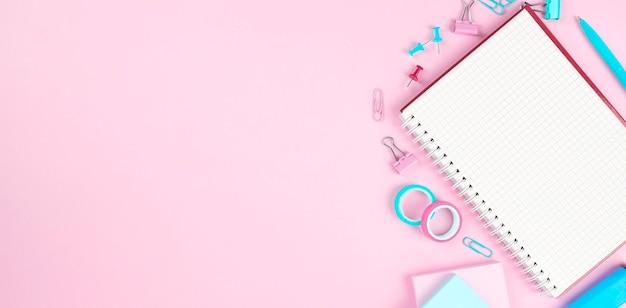 Articoli per ufficio della scuola su fondo rosa. torna al concetto di scuola. vista dall'alto.