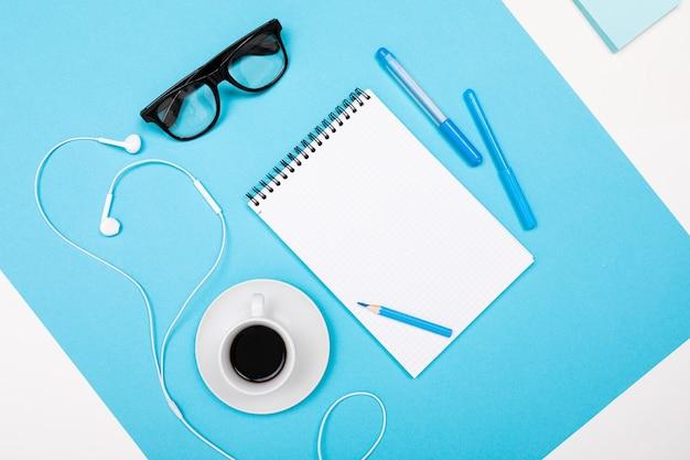 La scuola e le forniture per ufficio come banconote, penne, matite, calcolatrice, pennello, forbici, caffè, laptop giacciono ordinatamente su uno sfondo bianco e blu
