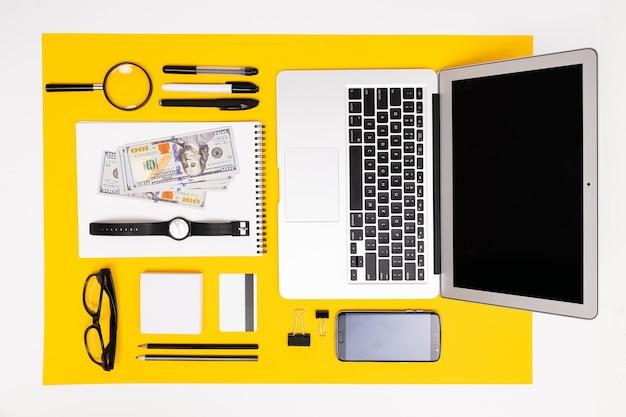 La scuola e le forniture per ufficio come banconote, penne, matite e altro si trovano ordinatamente su uno sfondo giallo