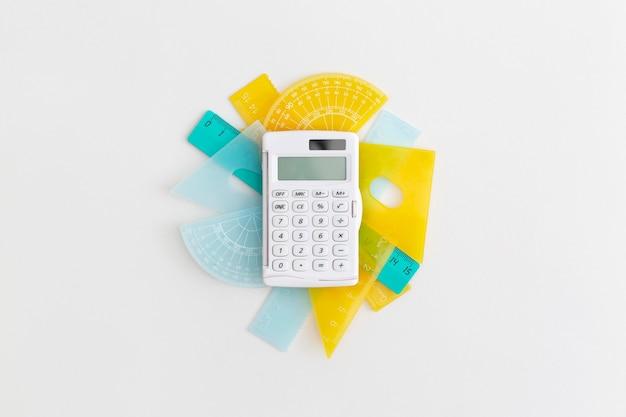 Righelli scolastici e calcolatrice su sfondo grigio torna al concetto di scuola