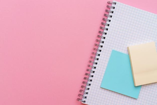 Quaderno a spirale scolastico su uno sfondo rosa gli adesivi giacciono sopra il foglio di cancelleria per appunti e...