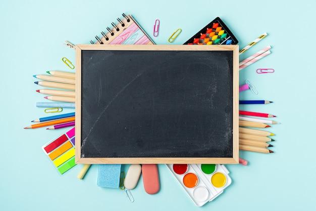Cancelleria scolastica sulla lavagna sfondo blu