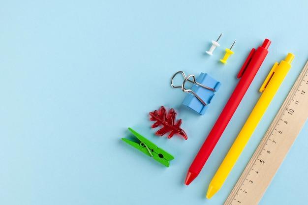 Cancelleria scolastica su sfondo blu. concetto di cartoleria, preparazione per la scuola, giornata della conoscenza.