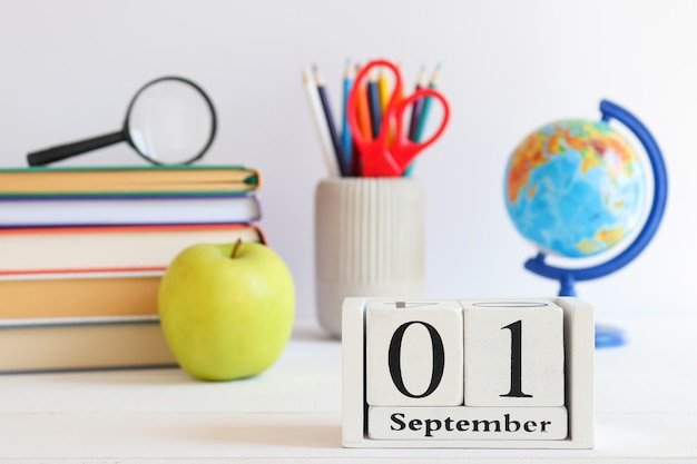 Mappamondo scuola cancelleria libri mela verde e calendario datato 1 settembre ritorno a scuola