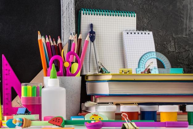 Cartoleria della scuola su un tavolo davanti alla lavagna.