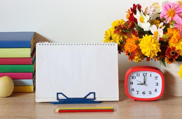 Scuola still life giorno della conoscenza copia spazio mockup composizione con un bouquet e libri di testo sul tavolo torna a scuola il 1 settembre