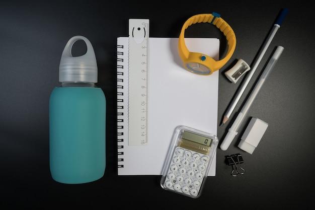 Rifornimenti di scuola su priorità bassa nera in studio. tavolo dello studente con materiale scolastico di base.