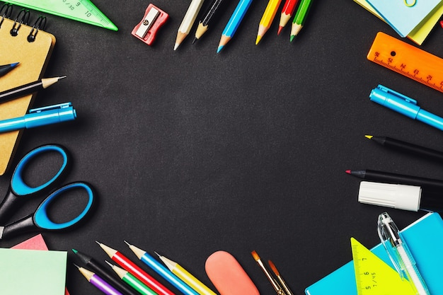 Forniture scolastiche sulla lavagna nera con spazio per il testo