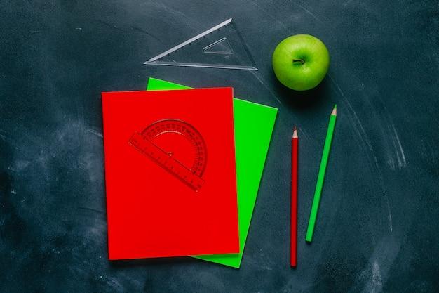 Materiale scolastico su un tavolo nero