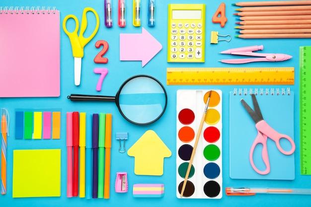 Forniture scolastiche su sfondo blu. torna al concetto di scuola.