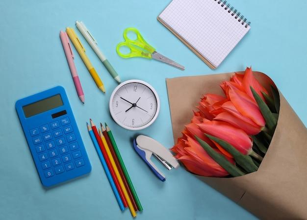 Materiale scolastico e un mazzo di tulipani rossi su un blu. ritorno a scuola, giornata della conoscenza o giornata dell'insegnante