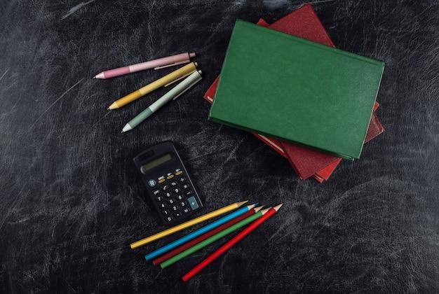 Forniture scolastiche su uno sfondo di lavagna. di nuovo a scuola. vista dall'alto.