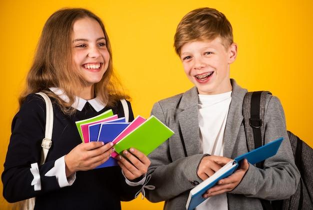 Materiale scolastico di cui i bambini hanno bisogno. i bambini felici tengono i taccuini. i bambini tornano a scuola. bambini piccoli durante l'orario scolastico. educazione e studio. cartoleria. 1 settembre