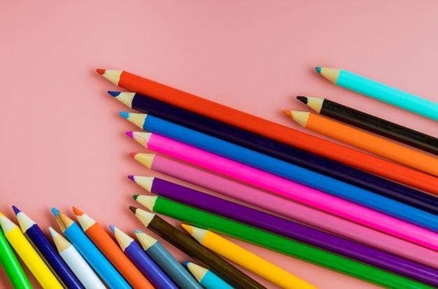 La cima colorata delle matite dei rifornimenti di scuola rasenta un fondo rosa