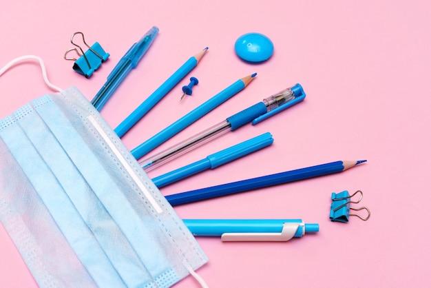 Materiale scolastico e strumenti di prevenzione del covid tornano a scuola durante il concetto di pandemia su un ba...