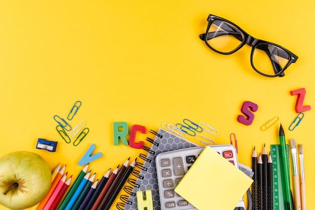 Rifornimenti e occhiali di scuola su giallo