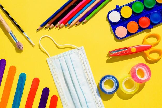 Forniture scolastiche accanto a una maschera per il viso, torna a scuola disteso