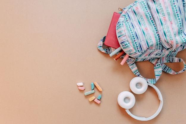 Materiale scolastico piatto giaceva su carta artigianale sfondo. zaino blu, cuffie bianche, taccuino e penne con lo spazio della copia.
