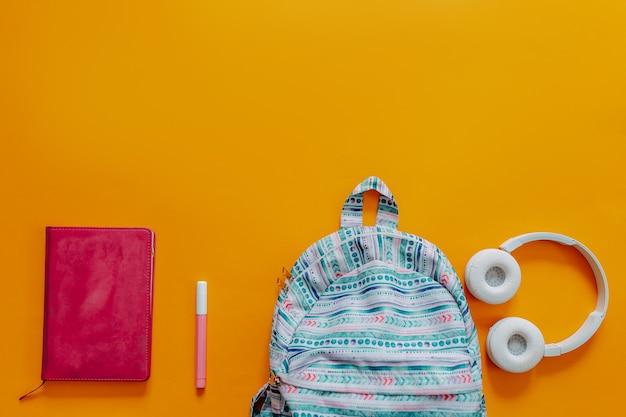 Materiale scolastico laici piatto sullo sfondo arancione. zaino blu, cuffie bianche, taccuino e penne.