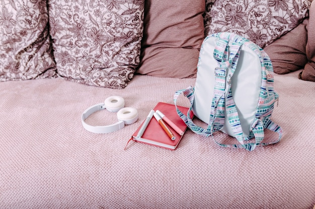 Materiale scolastico disteso sul divano dopo la scuola. zaino blu, cuffie bianche, taccuino e penne.