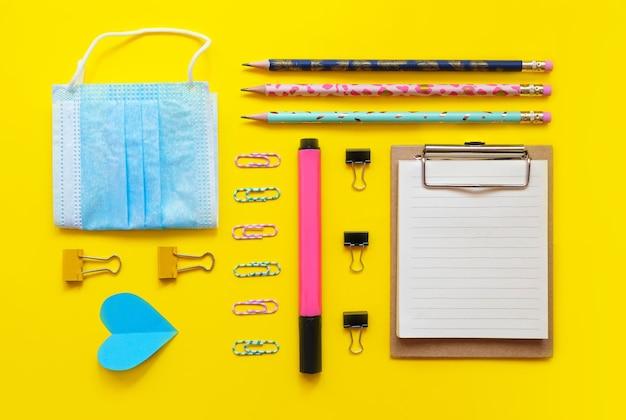 Forniture scolastiche flatlay su giallo