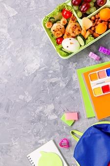 Materiale scolastico e lunchbox con cibo per bambini. disposizione variopinta della cancelleria su fondo multicolore, spazio della copia