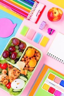 Materiale scolastico e lunchbox con cibo per bambini. disposizione variopinta della cancelleria su superficie multicolore, spazio della copia