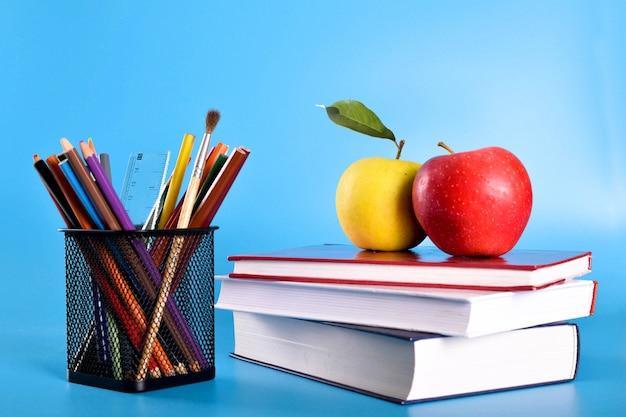 Materiale scolastico matite, penne, righello, pennello, libri e mela su blu