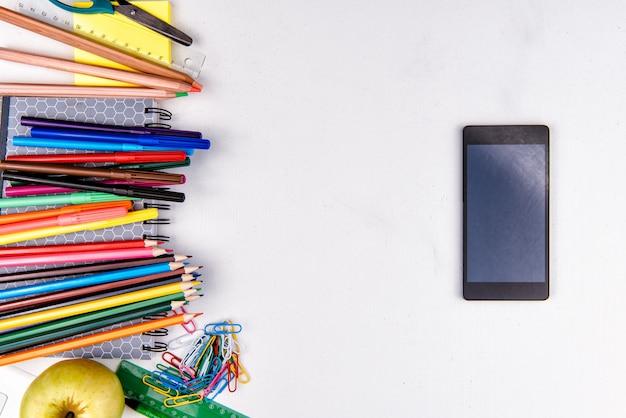 Rifornimenti e telefono di scuola su bianco