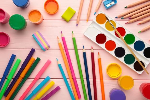 Forniture scolastiche su sfondo rosa. torna al concetto di scuola.