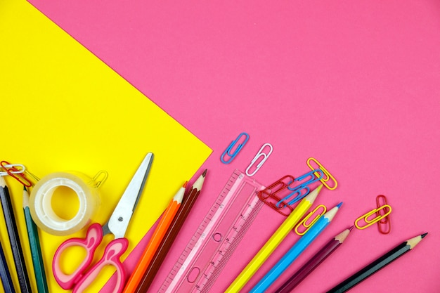 Materiale scolastico su sfondo di colore rosa. torna al concetto di scuola flatlay. articoli per la scuola.