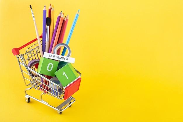 Materiale scolastico in un carrello della spesa e calendario in legno con la data del 1 settembre