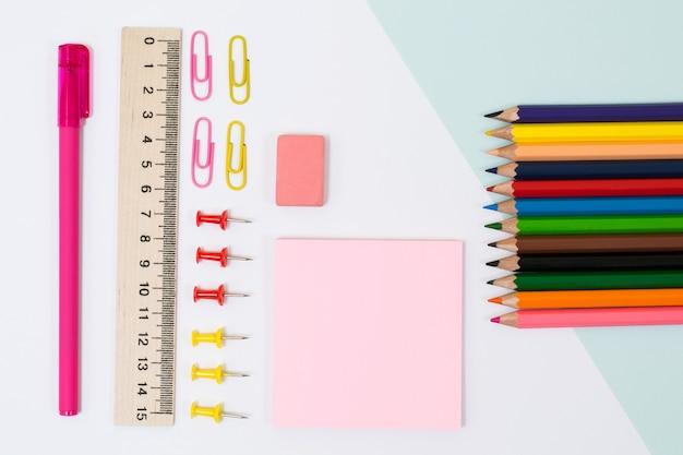 Materiale scolastico. foto vista dall'alto di adesivi, graffette e spilli, righello, gomma su sfondo bianco
