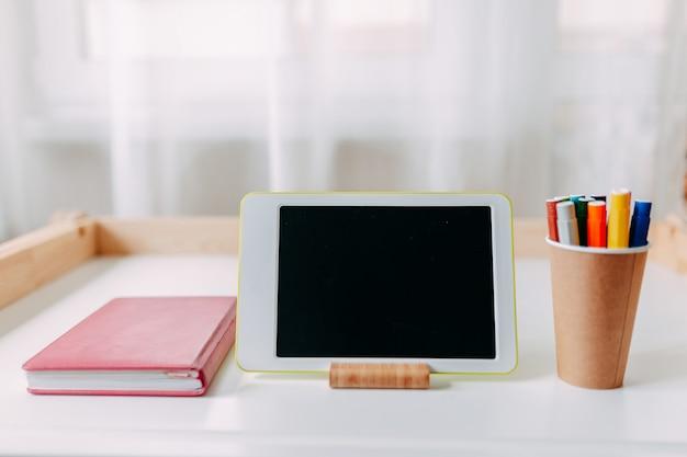 Forniture scolastiche sul tavolo bianco. tavoletta bianca, taccuino rosa, pennarelli sul tavolo.