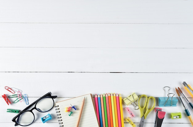 Rifornimenti di scuola su fondo di legno bianco con copyspace. istruzione o concetto di ritorno a scuola.