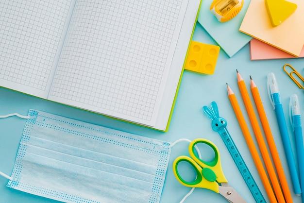 Materiale scolastico con maschera medica su blu, vista dall'alto